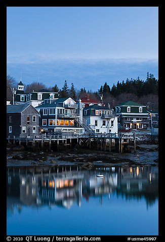 Houses with lights reflected in harbor. Stonington, Maine, USA (color)