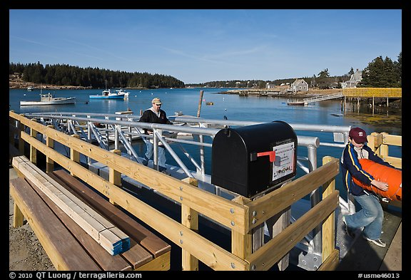Mailbox and people unloading mailboat. Isle Au Haut, Maine, USA (color)