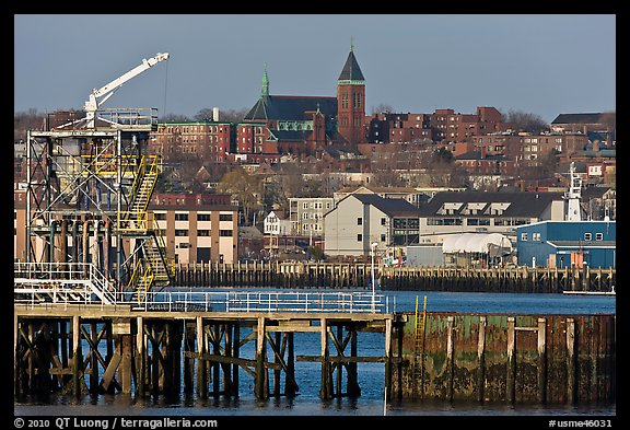 Pier and hillside buildings across harbor. Portland, Maine, USA (color)