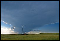 Windmill and tractor under a threatening stormy sky. North Dakota, USA