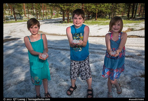 Children in summer dress holding large hailstones, Black Hills National Forest. Black Hills, South Dakota, USA (color)