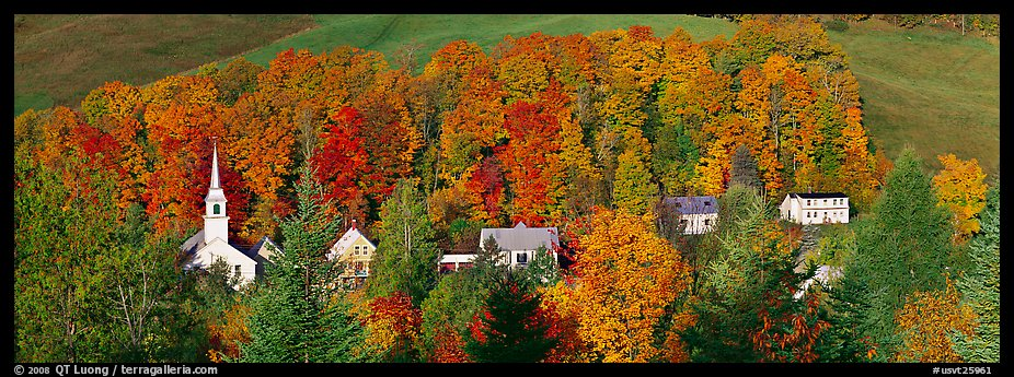 White-steppled church and houses amongst trees in fall foliage. Vermont, New England, USA (color)