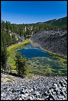 Pond at the edge of big obsidian flow. Newberry Volcanic National Monument, Oregon, USA