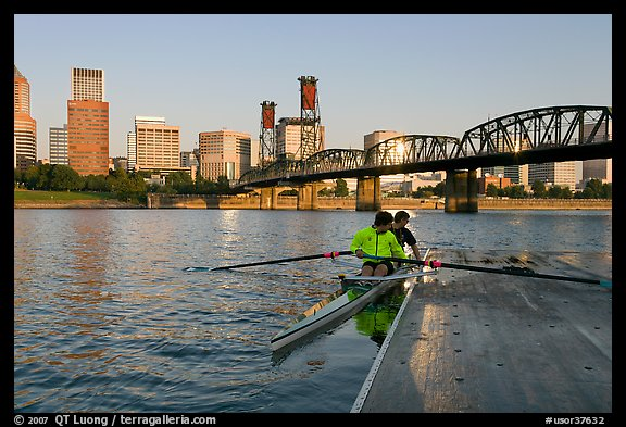 Rowers on double-oar shell lauching from deck in front of skyline. Portland, Oregon, USA (color)