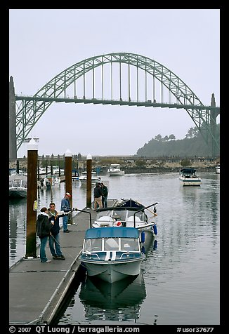 Couple holding small boat at boat lauch ramp. Newport, Oregon, USA (color)
