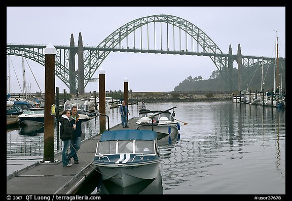 Couple holds  small boat on pier, Newport Marina. Newport, Oregon, USA (color)