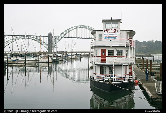 Couple walking on deck next to floating Bed and Breakfast. Newport, Oregon, USA (color)