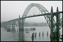 Small boat exiting harbor under Yaquina Bay Bridge. Newport, Oregon, USA (color)