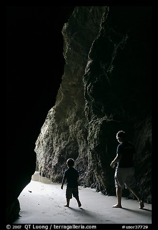 Father and son walking towards the light in sea cave. Bandon, Oregon, USA (color)