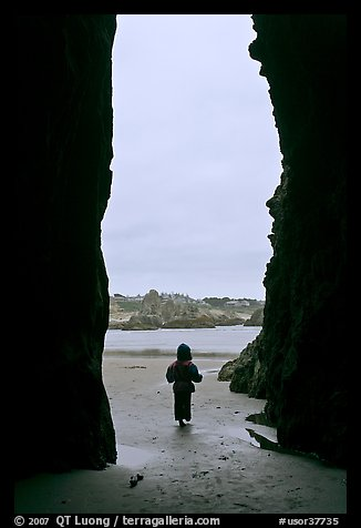 Infant standing at sea cave opening. Bandon, Oregon, USA (color)