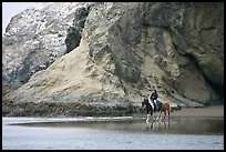 Woman horse-riding on beach next to sea cave entrance. Bandon, Oregon, USA (color)