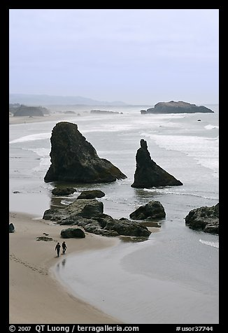 Beach with couple walking amongst sea stacks. Bandon, Oregon, USA (color)