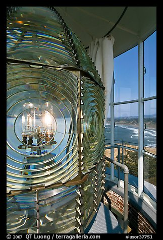 Rotating light inside Cape Blanco Lighthouse tower and landscape. Oregon, USA (color)