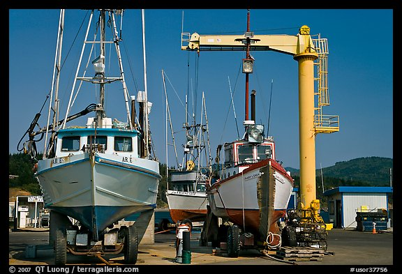 Fishing boats parked on deck with hoist behind, Port Orford. Oregon, USA (color)