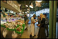 Countermen offer fish samples, Pike Place Market. Seattle, Washington (color)