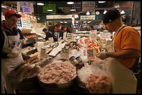 Countermen unloading seafood,  Pike Place Market. Seattle, Washington (color)