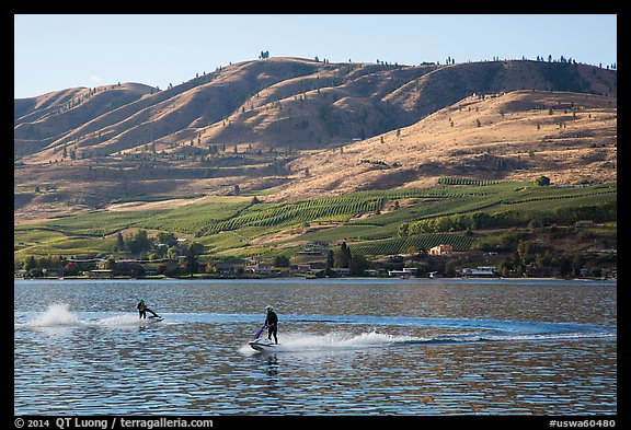 Personal watercraft riders and vineyard covered hills, Lake Chelan. Washington (color)