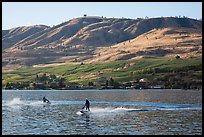 Personal watercraft riders and vineyard covered hills, Lake Chelan. Washington ( color)