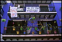 Facade of house painted in blue with pots, balconies and anti-war signs. San Juan, Puerto Rico (color)