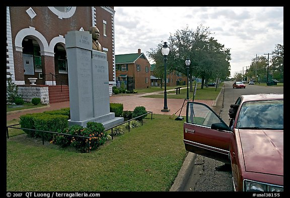 African-American man sitting in car looking at Martin Luther King memorial. Selma, Alabama, USA (color)