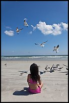 Girl sitting on beach with birds flying, Jetty Park. Cape Canaveral, Florida, USA ( color)