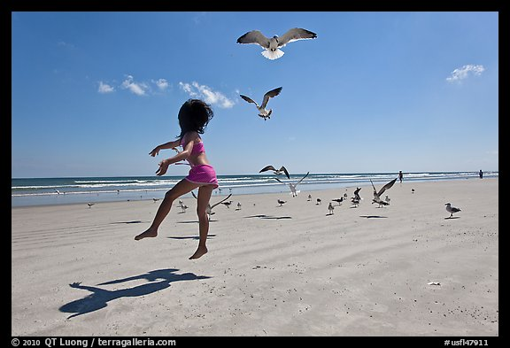 Girl jumping on beach with seagulls flying, Jetty Park. Cape Canaveral, Florida, USA (color)