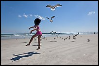 Girl jumping on beach with seagulls flying, Jetty Park. Cape Canaveral, Florida, USA ( color)