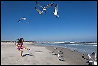 Beach with flying seagulls and girl, Jetty Park. Cape Canaveral, Florida, USA (color)