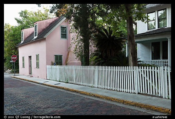 White picket fence and houses on cobblestone street. St Augustine, Florida, USA (color)