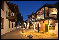 Old street and historic buildings with flags by night. St Augustine, Florida, USA ( color)