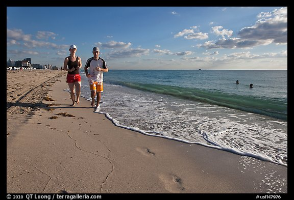 Couple jogging on beach,  Miami Beach. Florida, USA (color)