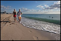 Couple jogging on beach,  Miami Beach. Florida, USA ( color)