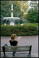 Woman reading a book in front of Forsyth Park Fountain. Savannah, Georgia, USA (color)