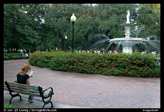 Forsyth Park Fountain with woman sitting on bench with book. Savannah, Georgia, USA (color)