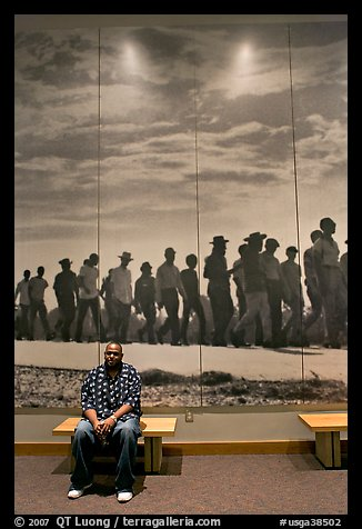 African American man sitting in front of march mural inside Martin Luther King, Jr. Visitor Center. Atlanta, Georgia, USA (color)