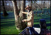 Bayou guide of French descent retriving net,  Lake Martin. Louisiana, USA (color)