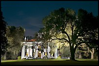 Antebellum mansion set in garden with  backlit oak tree at night. Natchez, Mississippi, USA