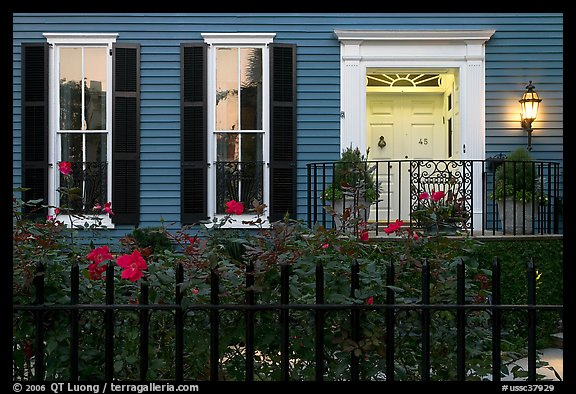 House facade at dusk with roses in front yard. Charleston, South Carolina, USA (color)