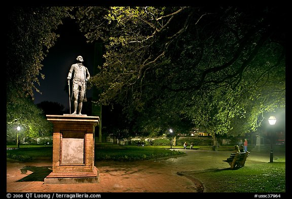 Park with statue and couples sitting on public benches at night. Charleston, South Carolina, USA (color)