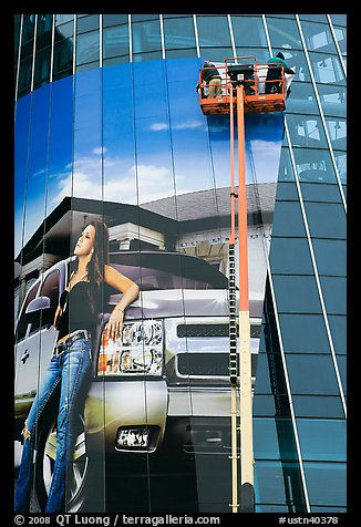 Workers pasting mural-sized car advertising on building. Nashville, Tennessee, USA (color)