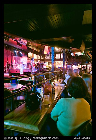 Patrons listen to musical performance in Beale Street bar. Memphis, Tennessee, USA (color)