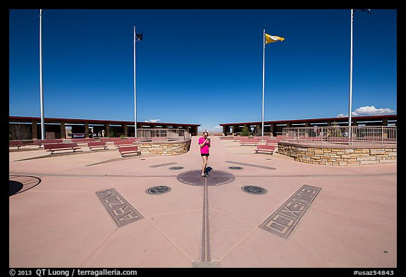 Woman straddling the territory of four states. Four Corners Monument, Arizona, USA (color)