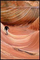 Hiker balances himself in the Wave. Vermilion Cliffs National Monument, Arizona, USA