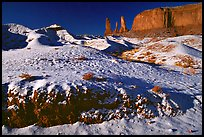 Snow on the floor, with Three Sisters in the background. Monument Valley Tribal Park, Navajo Nation, Arizona and Utah, USA