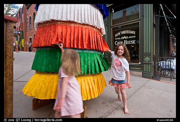 Girls spin tibetan prayer wheel. Telluride, Colorado, USA (color)