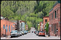 Historic brick buildings and slope with newly leafed aspens. Telluride, Colorado, USA ( color)