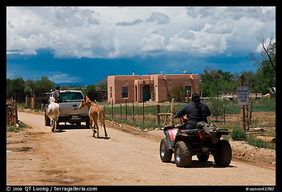 Rural road on the reservation with ATV, truck and horse. Taos, New Mexico, USA