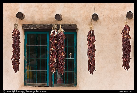 Yellow wall with ristras and blue window. Taos, New Mexico, USA (color)