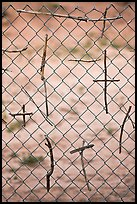 Crosses made of twigs on chain-link fence, Sanctuario de Chimayo. New Mexico, USA