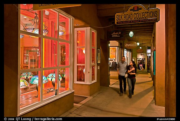 Couple walking by night in front of gallery. Santa Fe, New Mexico, USA